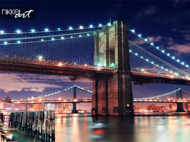 Brooklyn Bridge closeup over East River at night in New York City